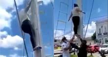 """Desorientada, mulher se pendura em mastro para """"arrancar"""" bandeira do Brasil e o que se vê a seguir é impressionante (veja o vídeo)"""