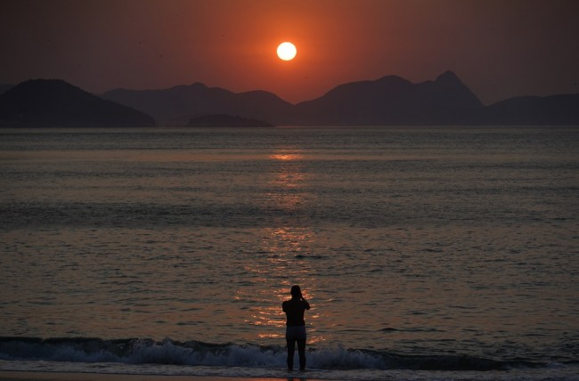 Homem entra na água para registrar o nascer do sol, no dia que pode ser o mais quente do ano no Rio — Foto: Marcos Serra Lima/G1