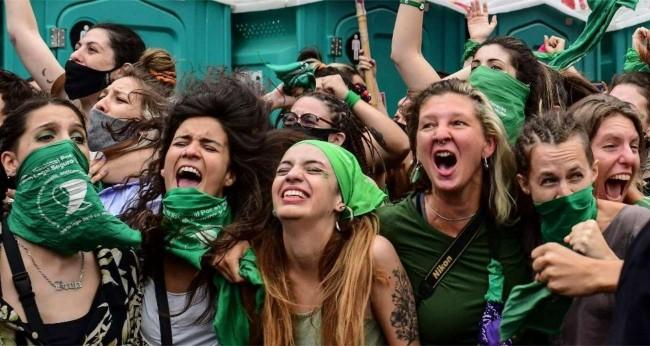 Mulheres celebram aprovação na Câmara; as máscaras verdes são o símbolo das ativistas que defendem o direito ao aborto / Imagem: RONALDO SCHEMIDT/AFP